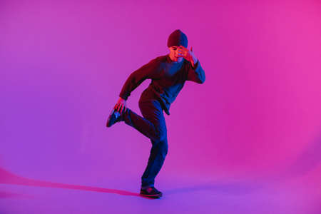 Young Man in a Jumper Dancing Contemporary Dance in Studio. Breakdancing. Dance School Poster. Copy Space. Battle competition announcement. Pink and Blue Background