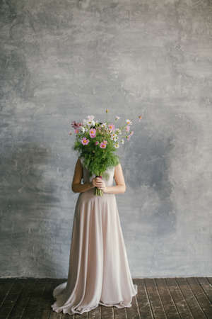 Young Beautiful Girl in a Pink Dress with a Bouquet Covers her Face on a Gray Background.