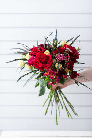 Beautiful bouquet of mixed flowers with peonies. The work of the florist. Flower delivery Zdjęcie Seryjne