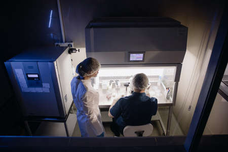 In a Modern Laboratory Scientist Conduct Experiments. Embryologist Examines Samples with a Microscope Zdjęcie Seryjne