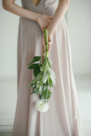 Young Beautiful Girl in a Pink Dress with a Bouquet Holding a Delicate Bouquet of Flowers on a Gray Background.