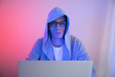 Gamer plays on a laptop. The programmer writes the code. Man on a colored background
