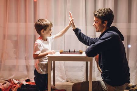 Father and Son play a Board Game in a Cozy Room