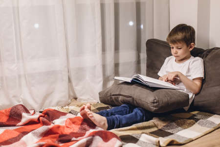 Little boy Reading a Book in a Cozy Room 版權商用圖片 - 148075326