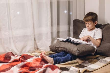 Little boy Reading a Book in a Cozy Room Foto de archivo