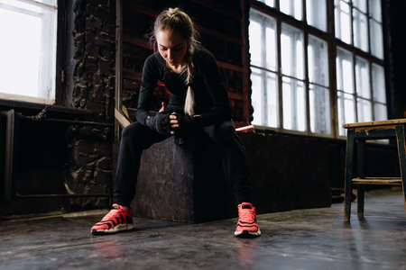 Girl fighter bandages her hands before training in the gym. Red Neon Light