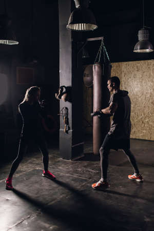 Man and girl fighter in boxing bandages trains in gym. Mixed martial arts 版權商用圖片