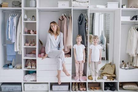 Female wardrobe. Stylish mother, cute twin daughters wearing comfortable home clothes posing in closet. Happy motherhood 版權商用圖片