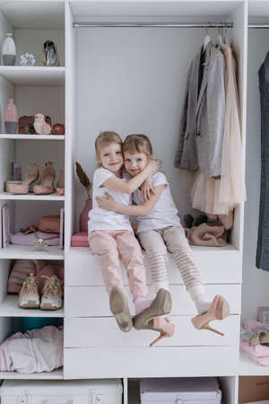 Family wardrobe. Happy twin sisters on shelve in closet with natural organic clothes in cozy dressing room play joyfully 版權商用圖片