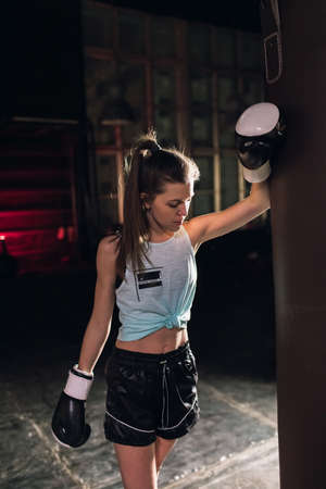 cool female fighter in boxing gloves trains in the gym. Mixed martial arts 版權商用圖片