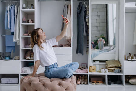Young woman sits in a modern dressing room with a phone taking a selfie 版權商用圖片