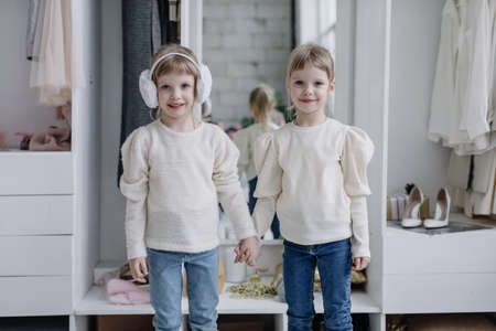 Girls sisters stand in a modern dressing room and look at the camera