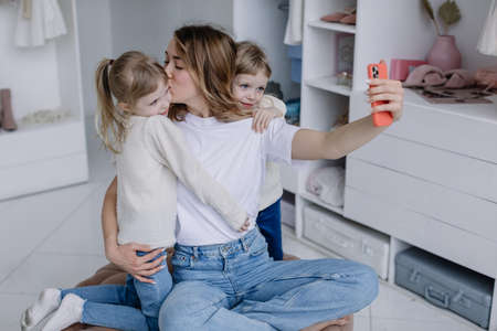 Young mother sits in a modern dressing room with a phone taking selfies with her twin daughters