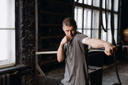 Cool man fighter in boxing bandages trains in the gym. Mixed martial arts 版權商用圖片