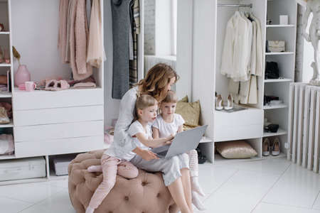 Young mother with her twin daughters choose things online in her cozy apartment