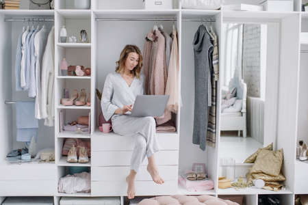 Young woman chooses things online from the comfort of your dressing room. Online shopping 版權商用圖片