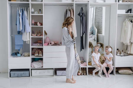 Young woman chooses a dress in her modern dressing room. Mom shows her daughters a dress