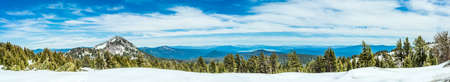 Mountains, lakes, and a forest with snow - photographed as a wide panorama at Lassen Volcanic National Park in Northern California