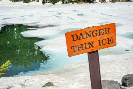 Thin ice warning notice on orange danger signboard by mountain lake Stok Fotoğraf