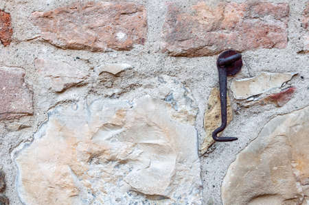 Typical wall made of stones and bricks of ancient Italian house, with rusty iron door hook.