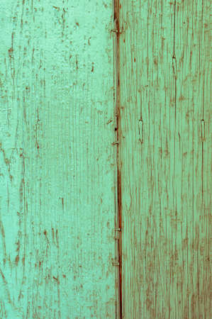 Wooden panels and planks of rural house door, Italy. Walls and ornaments in painted wood for the country house, ruined by time. Stock Photo
