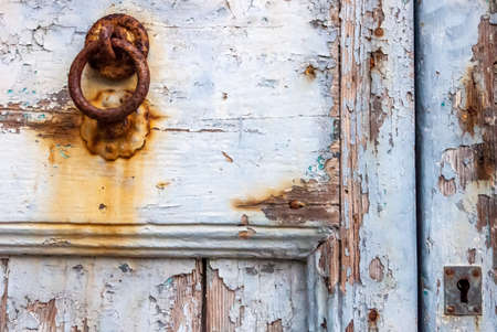 Ancient Italian house: detail of the typical painted wooden door, eroded by time, with a rusty iron knocker. Stockfoto