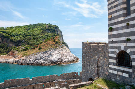 Portovenere, Italy. Beautiful seaside village with the famous gulf of poets that inspired the poems of Byron, a popular tourist destination for beach holidays and tracking in unspoiled nature. Church of San Pietro and Island of Palmaria. Stockfoto
