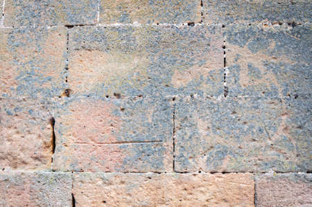 Typical detail of an old wall of an Italian house, made of hand-carved stones eroded by time.