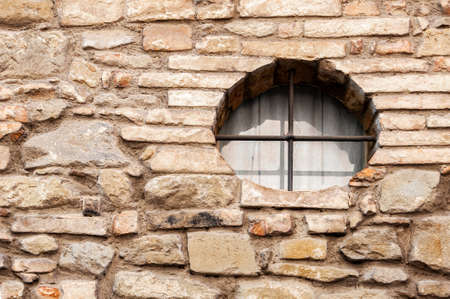 Typical detail of an old wall of an Italian house with a circular window, made of hand-carved stones eroded by time.