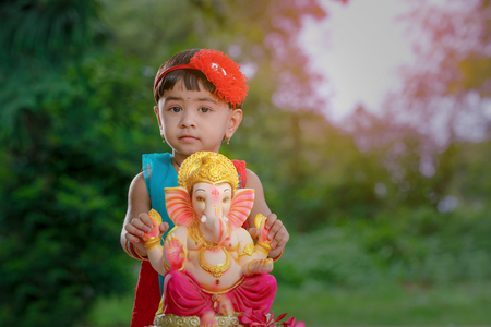 Little Indian girl child with lord ganesha and praying , Indian ganesh festival Stock Photo