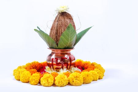 Kalash di rame con cocco, foglia e decorazioni floreali su sfondo bianco. essenziale nella puja indù.