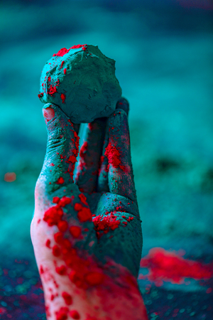Hand holding a ball of colored powder during Holi festival