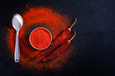 Red Chili pepper flakes and chili powder burst on black background Banco de Imagens - 124972575