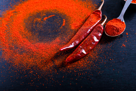 Red Chili pepper flakes and chili powder burst on black background