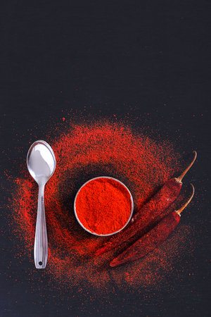 Red Chili pepper flakes and chili powder burst on black background Banco de Imagens - 124972578