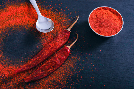 Red Chili pepper flakes and chili powder burst on black background Banco de Imagens - 124972580