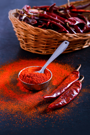 Red Chili pepper flakes and chili powder burst on black background Banco de Imagens - 124972603