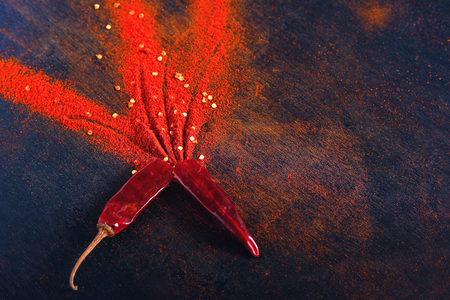Red Chili pepper flakes and chili powder burst on black background Banco de Imagens - 124972604