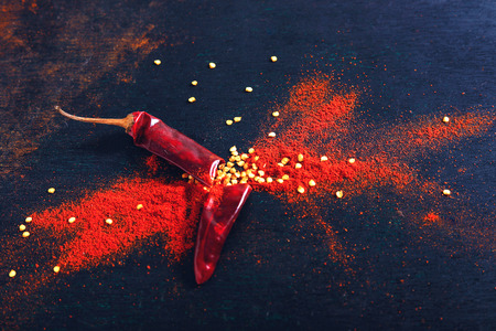 Red Chili pepper flakes and chili powder burst on black background Banco de Imagens - 124972605