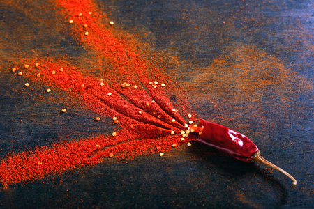 Red Chili pepper flakes and chili powder burst on black background Banco de Imagens - 124972615