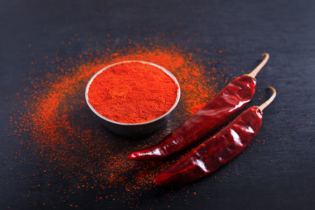 Red Chili pepper flakes and chili powder burst on black background Banco de Imagens - 124972627