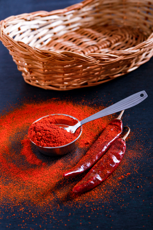 Red Chili pepper flakes and chili powder burst on black background Banco de Imagens - 124972628