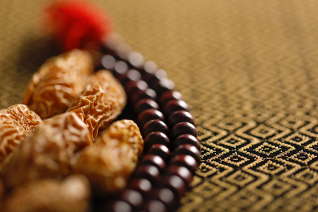 Date fruits with an Islamic prayer beads on an artistic background. Beautiful background for Ramzan or Ramadan.