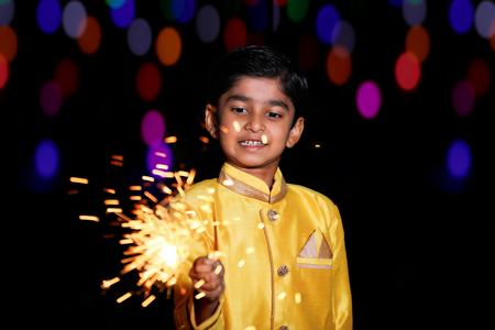 Cute Indian child celebrating Diwali festival with cracker and sparkle