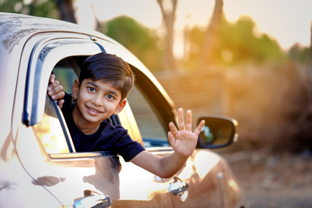 Cute Indian Child waving from car window