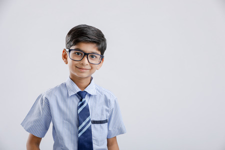 Śliczny mały indyjski / azjatycki chłopiec w mundurze i okularach