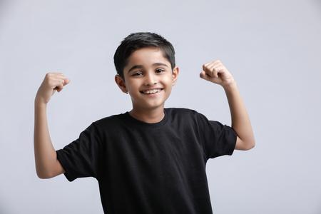 kleine Indiase / Aziatische jongen die houding op een witte achtergrond toont