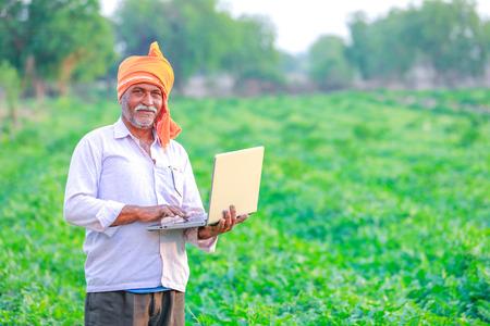 Indian rural farmer using laptop Imagens