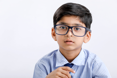 Cute little Indian / Asian school boy wearing uniform and spectacles