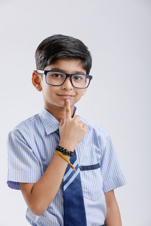 Cute little indian school boy asking / posing to keep silence, standing isolated over white background 版權商用圖片